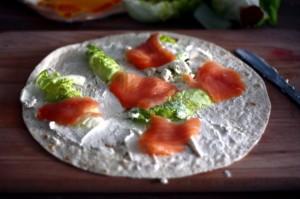 Położone na tortilli składniki - wędzony łosoś, serek chrzanowy i sałata rzymska